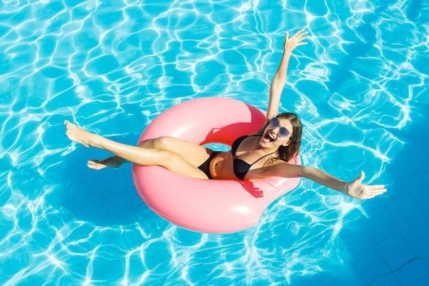 Schöne verrückte frau, die auf aufblasbarem ring im blauen swimmingpool sich entspannt