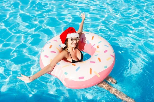 Schöne verrückte frau in santa claus-hut, der auf aufblasbarem ring im blauen swimmingpool sich entspannt