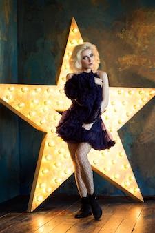 Schöne verspielte erwachsene blonde frau, die dunkelblauen spitzen-tutu-rock und netzstrümpfe trägt, die über dunkler wand mit leuchtendem stern aufwerfen. schauspielerin spielt auf der bühne