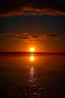 Schöne vertikale aufnahme des roten sonnenuntergangs mit wolken am himmel mit reflexion im wasser