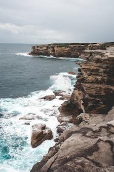 Schöne vertikale aufnahme einer großen klippe neben blauem wasser an einem trüben tag