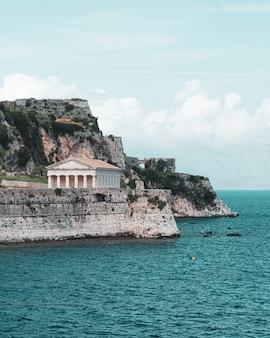 Schöne vertikale aufnahme eines alten tempels und des meeres in einer der griechischen inseln