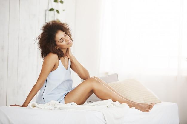 Schöne verträumte afrikanische frau in der nachtwäsche mit den geschlossenen augen träumend thiking sitzend auf bett.