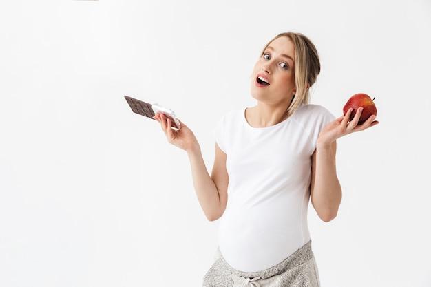 Schöne verwirrte schwangere frau, die zwischen schokoriegel und rotem apfel lokalisiert auf weißem hintergrund wählt