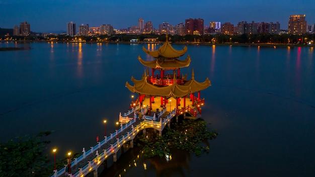 Schöne verzierte pagode des traditionellen chinesen mit kaohsiung-stadt im hintergrund nachts, wuliting, kaohsiung, taiwan.