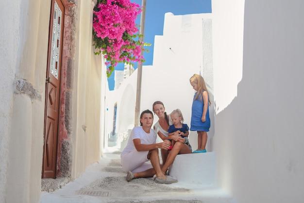 Schöne vierköpfige familie, die auf haustür am alten griechischen haus in der straße emporio, santorini sitzt