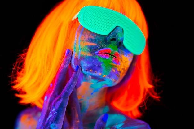 Schöne vorbildliche frau in perücke und brille mit buntem hellem fluoreszierendem make-up im neonlicht, nachtclubdisco.