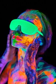 Schöne vorbildliche frau mit brille mit buntem, hellem fluoreszierendem make-up im neonlicht, nachtclubdisco.