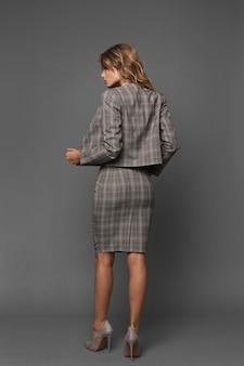 Schöne vorbildliche frau mit perfektem körper und sexy beinen in formeller kleidung auf grauem hintergrund. junge geschäftsfrau in einem trendigen anzug und schuhen der hohen absätze, die mit ihrem rücken am grauen hintergrund aufwerfen.