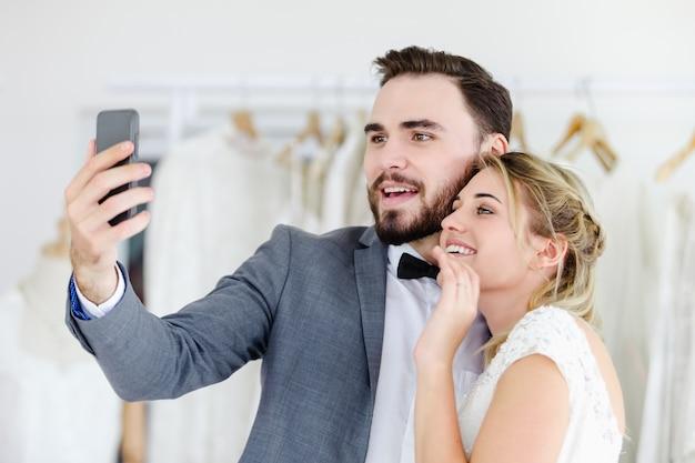 Schöne vorbildliche hochzeitspaare, die smartphone on-line-videoanruf betrachtet schirm halten