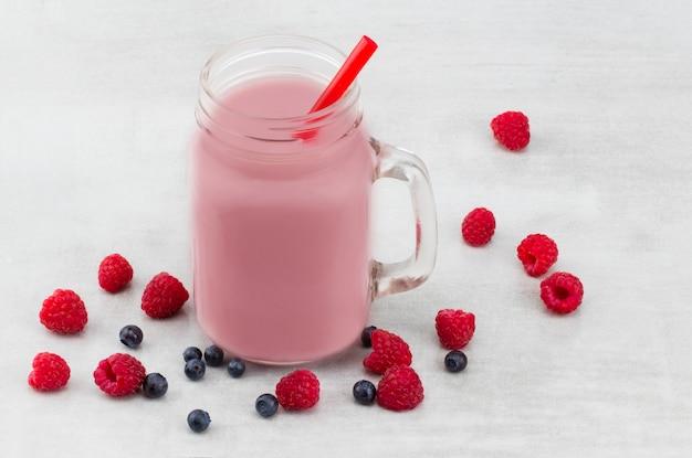 Schöne vorspeise rosa himbeeren und heidelbeerfrucht smoothie oder milchshake im glas mit beeren.
