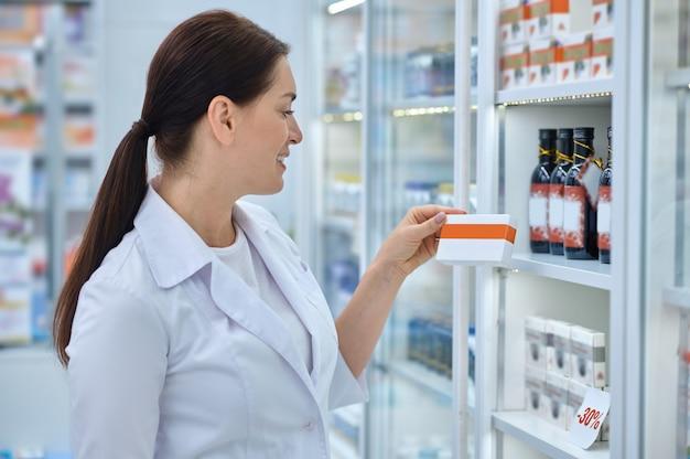 Schöne wahl. profil einer lächelnden frau im medizinischen kittel mit langen dunklen haaren mit einer medikamentenschachtel, die in der nähe des regals in der apotheke steht
