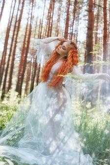 Schöne waldnymphe der rothaarigen frau in einem blauen transparenten hellen kleid in den wäldern, die im tanz drehen. mädchen mit roten haaren