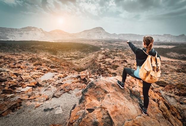 Schöne wanderfrau auf der spitze des berges, der auf das sonnenuntergangstal zeigt. mädchen mit rucksack reisen allein in der natur.