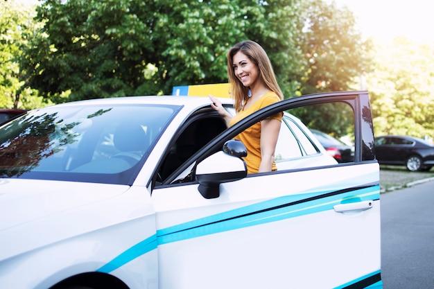 Schöne weibliche autofahrschülerin, die fahrzeug auf ihrer ersten klasse betritt.
