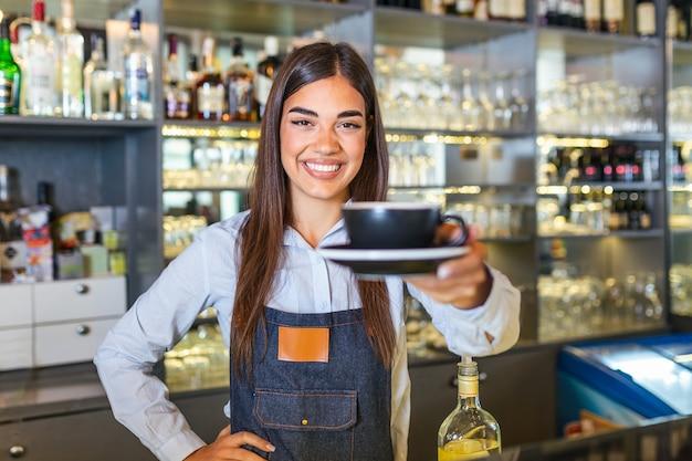 Schöne weibliche barista hält eine tasse mit heißem kaffee