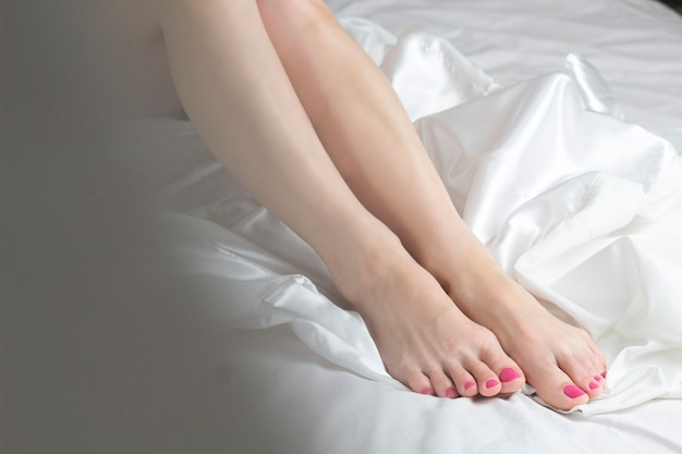 Schöne weibliche beine auf weißem gewebe. fußpflege.
