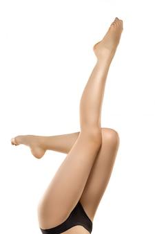 Schöne weibliche beine, gesäß und bauch lokalisiert auf weißem raum