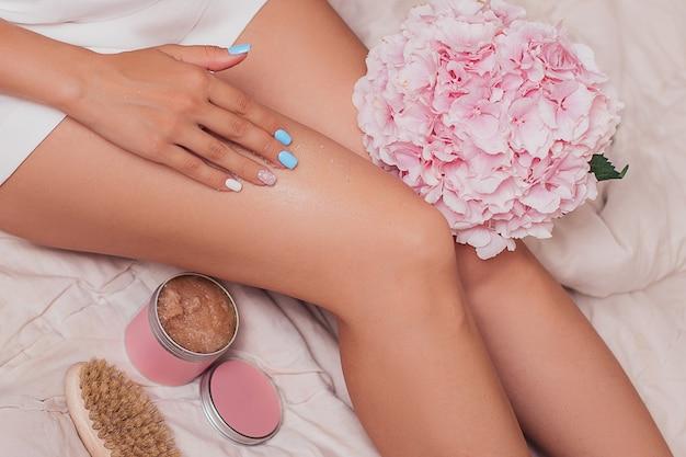 Schöne weibliche beine im bett liegend mit peeling und körperbürste für massage