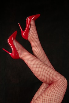Schöne weibliche beine in netzstrümpfen und roten schuhen