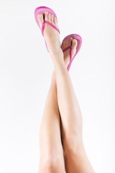 Schöne weibliche beine mit flip-flops. isoliert auf weiß