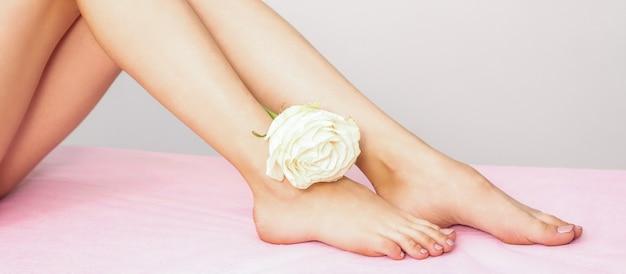 Schöne weibliche beine mit weißer rose nach enthaarung auf rosa bettlaken gegen eine graue wand