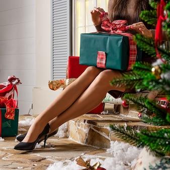 Schöne weibliche beine nahe weihnachtsbaum mit geschenkboxen