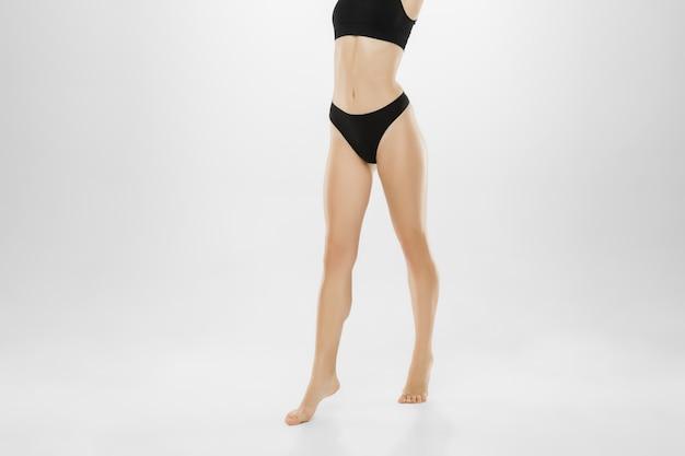 Schöne weibliche beine und bauch lokalisiert auf weißem hintergrund. beauty-, kosmetik-, spa-, enthaarungs-, behandlungs- und fitnesskonzept.