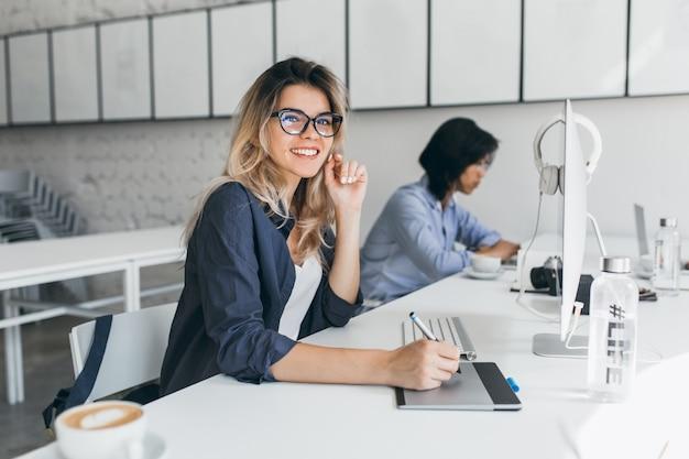 Schöne weibliche büroangestellte, die verwaltungsarbeit für firma ausführt
