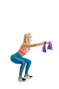 Schöne weibliche fitnesstrainer üben isoliert auf weißer wand
