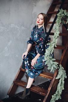 Schöne weibliche frau im dunkelblauen kleid, das auf hölzerner treppe sitzt.