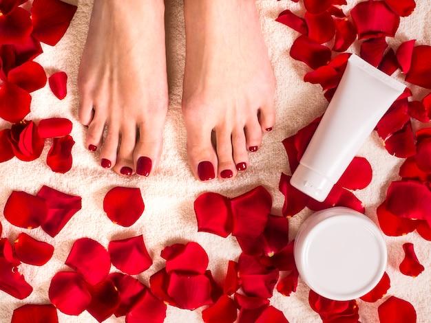 Schöne weibliche füße auf frotteetuch mit rosenblättern. glas und tube hautpflegecreme. spa- und hautpflegekonzept