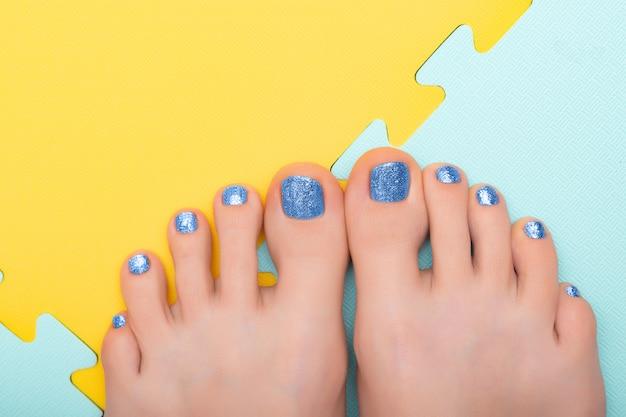 Schöne weibliche füße mit blauer funkelnpediküre