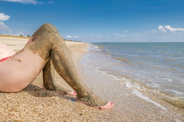 Schöne weibliche füße mit leuchtend roter pediküre auf dem strandsand