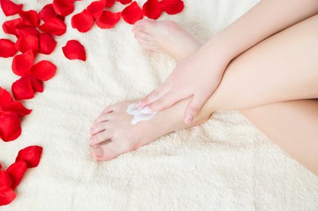 Schöne weibliche füße und rosenblätter