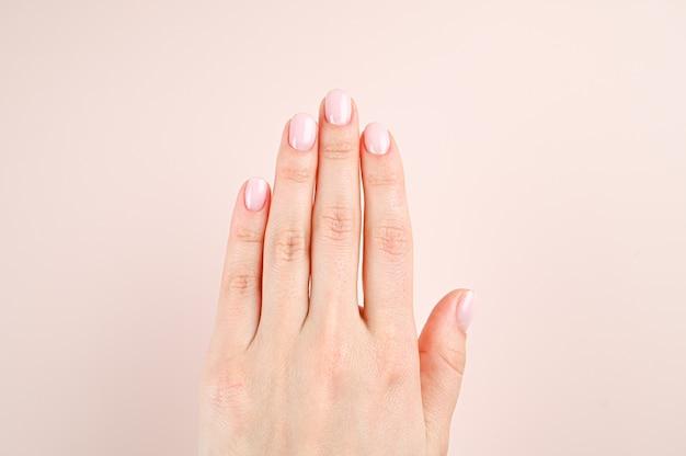Schöne weibliche hände, auf einem hintergrund der beige farbe