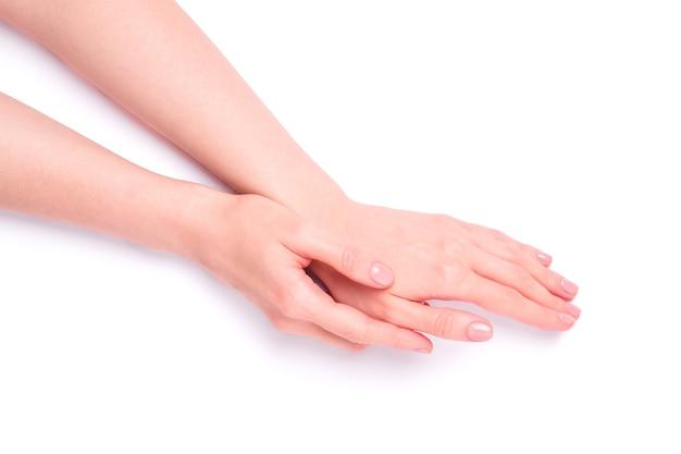 Schöne weibliche hände, die frische niedliche rosa maniküre zeigen