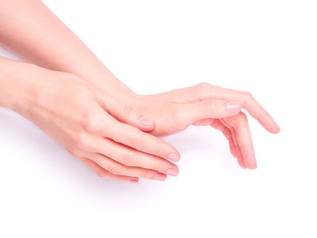 Schöne weibliche hände, die frisches niedliches rosa maniküre-, haut- und nagelpflegekonzept zeigen