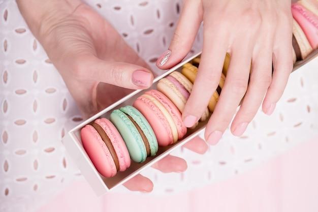Schöne weibliche hände, die geschenkbox der köstlichen französischen bunten makronen halten