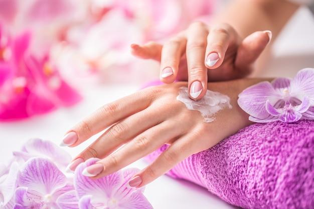 Schöne weibliche hände, die handcreme auftragen. lila handtuch und orchideendekoration. gesundes konzept - nails spa hautpflege und wellness.