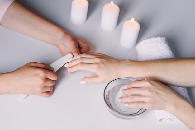Schöne weibliche hände, die spa-maniküre im schönheitssalon haben. nägel polieren mit nagelfeilen.