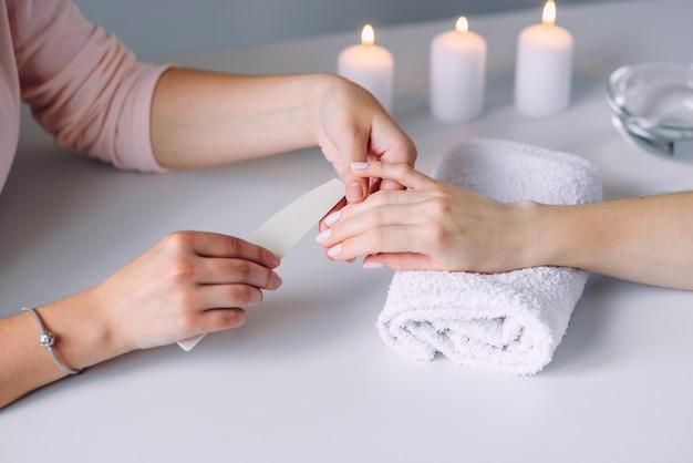 Schöne weibliche hände, die spa-maniküre im schönheitssalon haben. poliert nägel mit nagelfeilen.