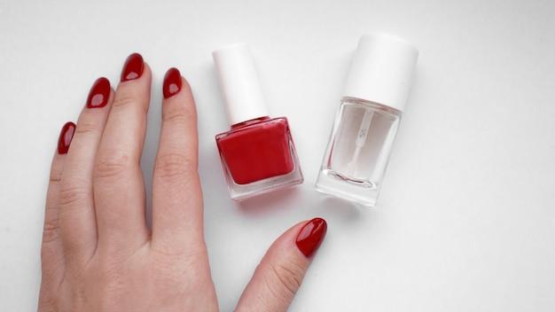 Schöne weibliche hände. hautpflege für die hände. schöne frauenhände mit roter maniküre. roter nagellack und nagelhautöl.