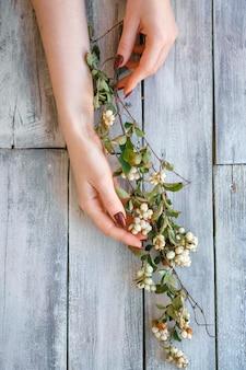 Schöne weibliche hände liegen mit blumen auf hölzernem hintergrund, handhautpflege, schöne maniküre