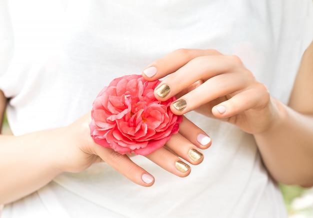 Schöne weibliche hände mit perfektem goldenen und rosa nageldesign halten frische rosenblume