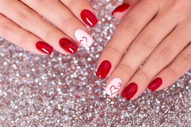Schöne weibliche hände mit roter maniküre, herzentwurf, auf silbernem hintergrund