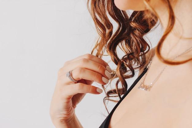 Schöne weibliche hände mit weißer maniküre und verlobungsring,