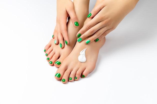 Schöne weibliche hände tragen creme auf ihre füße auf