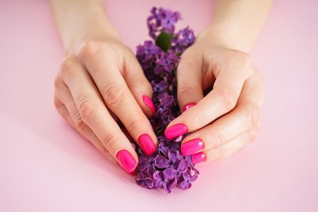 Schöne weibliche hände und ein zweig flieder auf einem rosa hintergrund. schönheits- und hautpflegekonzept. schöne maniküre nahaufnahme.