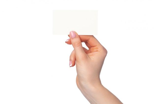 Schöne weibliche hand, die weiße visitenkarte auf weiß hält